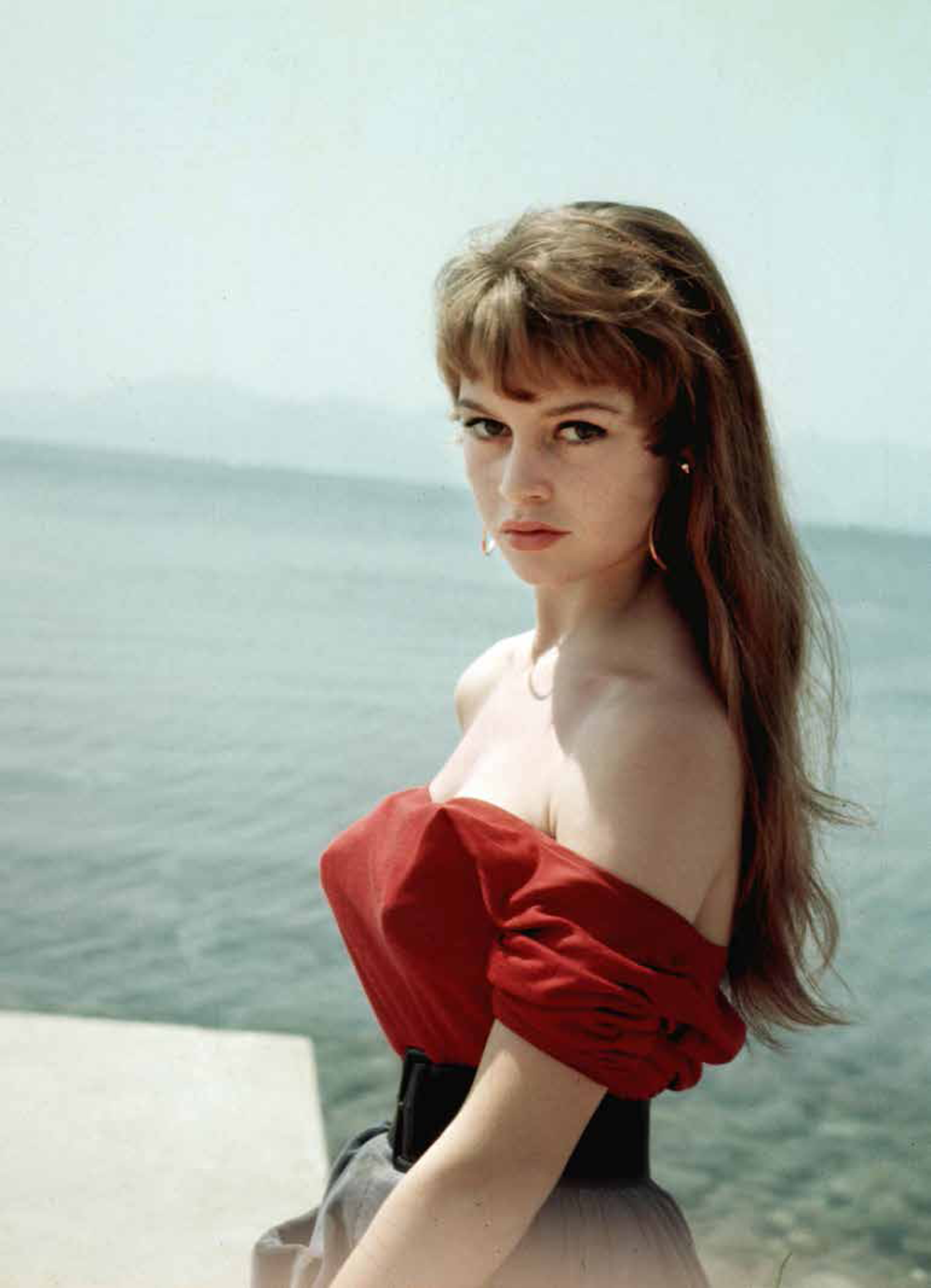At the Cannes International Film Festival, 1953. The off-theshoulder neckline became the Bardot neckline. Worn with a flared mid-length skirt, finished off with a waist-cinching belt. © Kary H. Lasch, from Brigitte Bardot: My Life in Fashion (Flammarion, 2016).